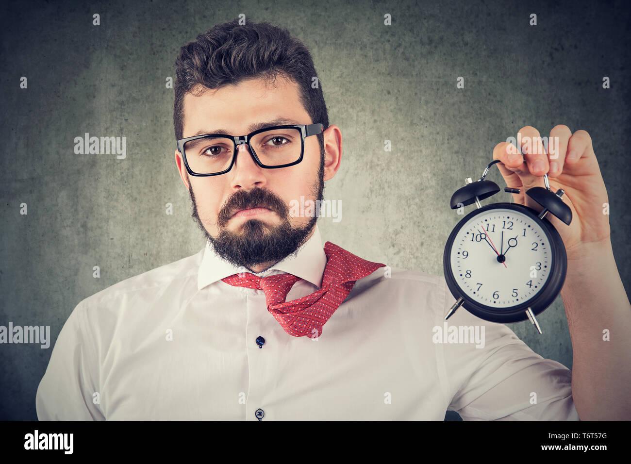 Sad overworked business man with alarm clock - Stock Image