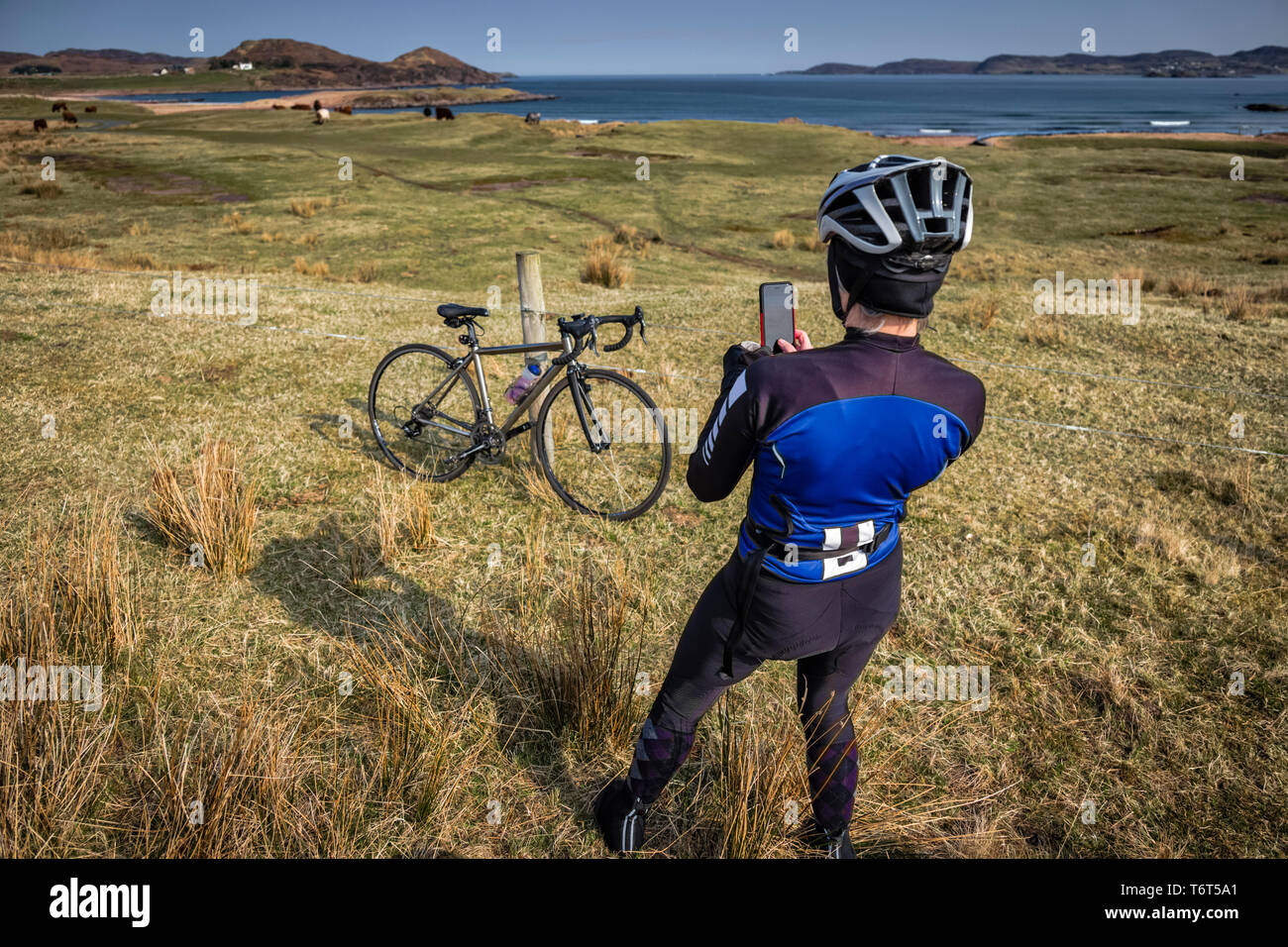Female cyclist captures the beauty of the landscape along Loch Ewe, Poolewe, west coast of Scotland, UK. Stock Photo