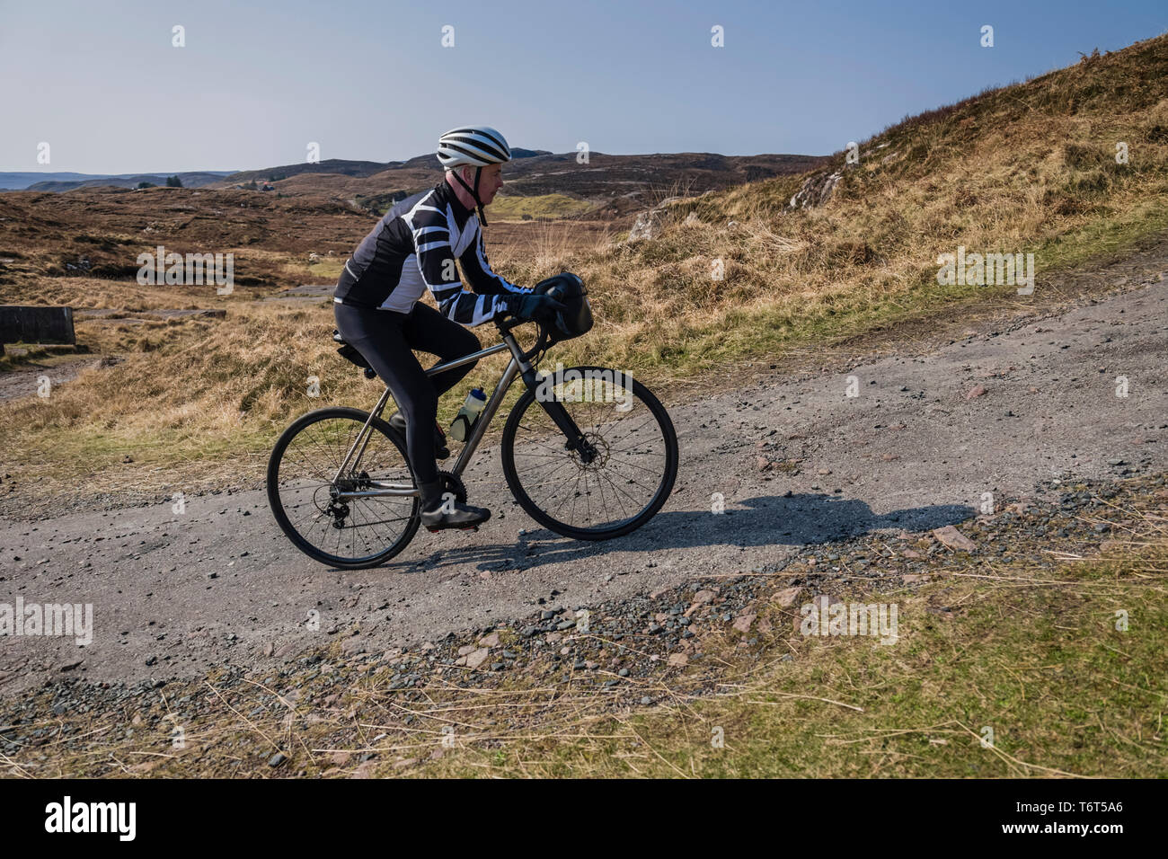 Mature male cyclist riding up a gravel track close to Poolewe, west coast of Scotland. Stock Photo