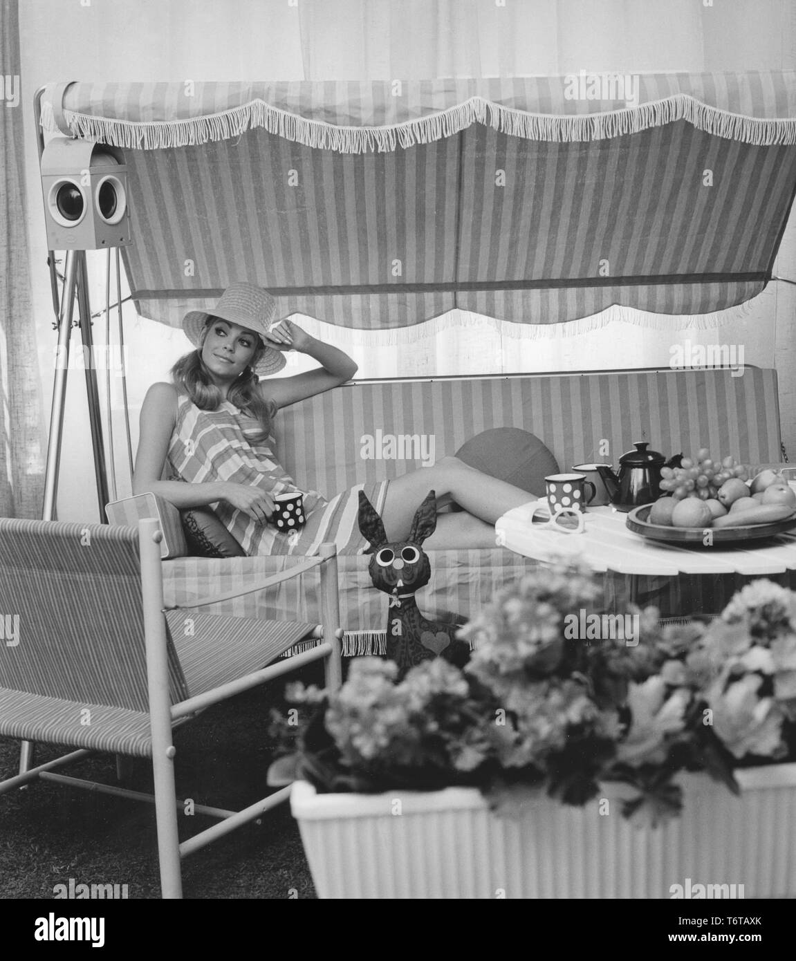 Summer of the 1960s. A young woman is sitting comforably in a hammock drinking coffe. The design of the furniture and her dress represents the 1960s decade very well. Sweden 1960s Stock Photo