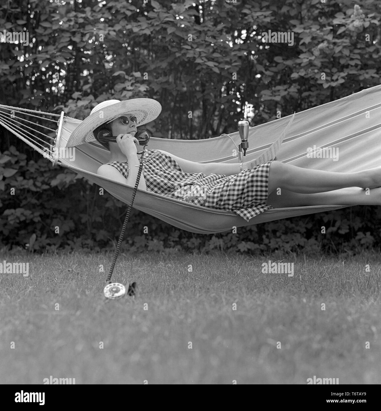 Summer in the 1960s. A lady is lying comfortably in a hammock talking on the phone.  Sweden 1961 - Stock Image