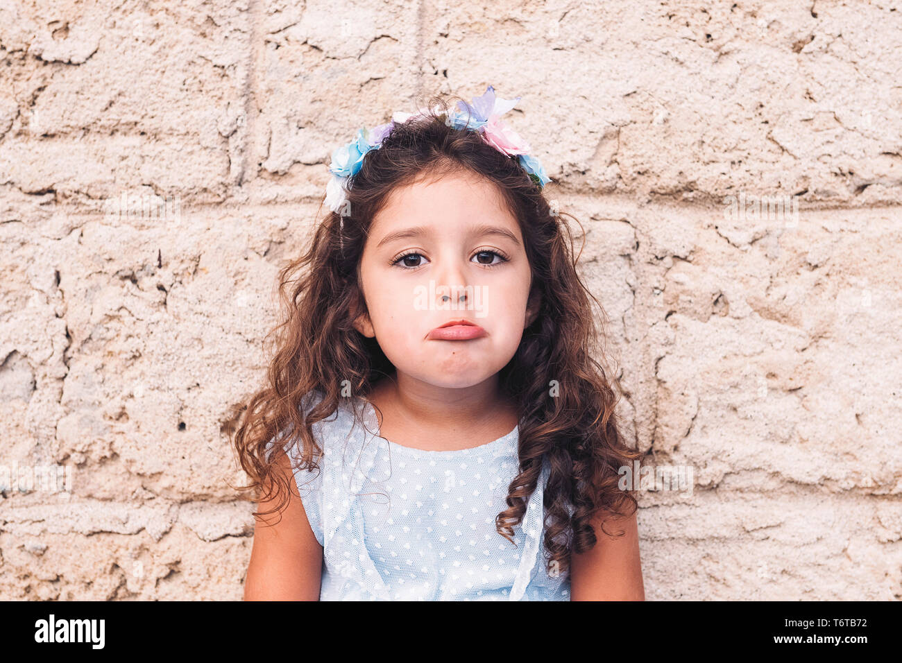 little girl making teasing with sad face, is in front of a stone wall and wears a blue dress and a flower headband Stock Photo