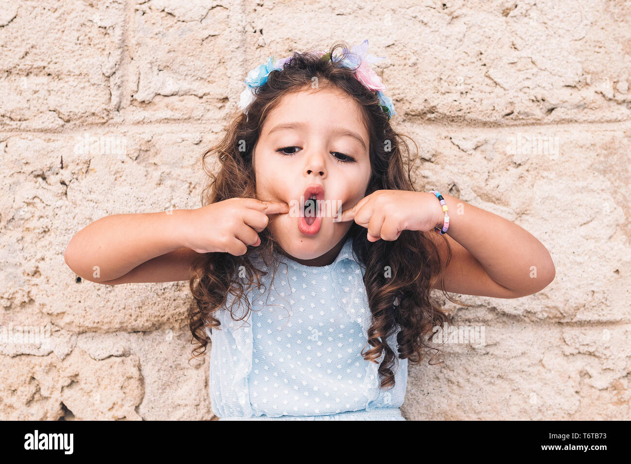 little girl making fun with her face, is in front of a stone wall and wears a blue dress and a flower headband - Stock Image