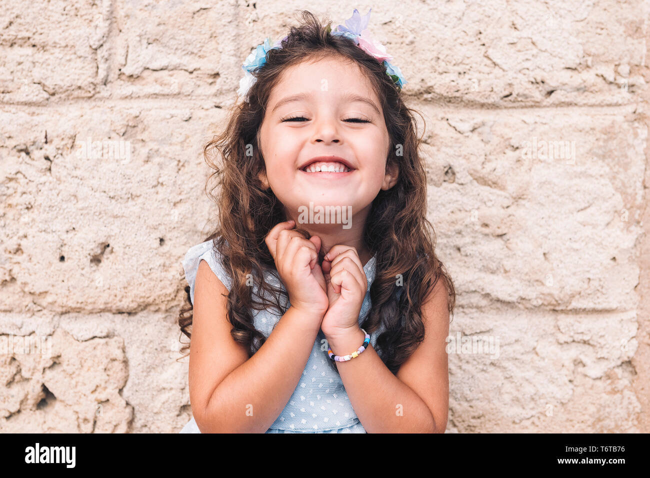 little girl smiles funny, is in front of a stone wall and wears a blue dress and a flower headband - Stock Image