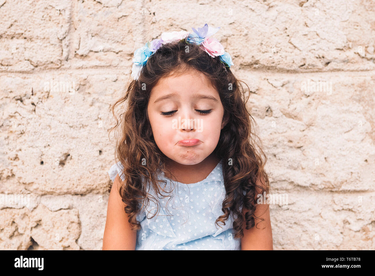 little girl making fun with sad face, is in front of a stone wall and wears a blue dress and a flower headband Stock Photo