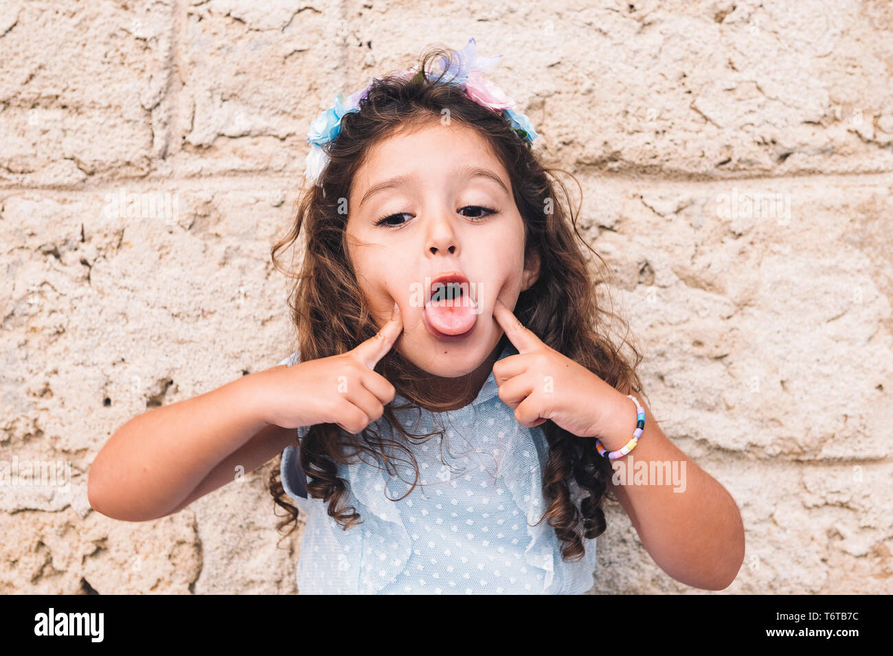 little girl making fun with her tongue, is in front of a stone wall and wears a blue dress and a flower headband - Stock Image