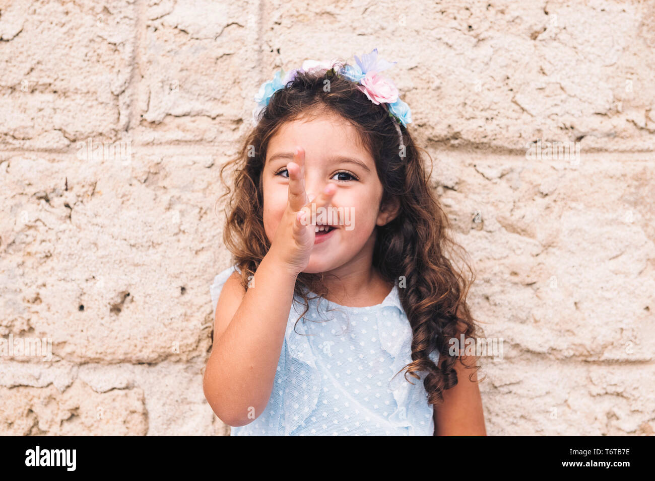 little girl making fun with her hand on her nose, is in front of a stone wall and wears a blue dress and a flower headband - Stock Image