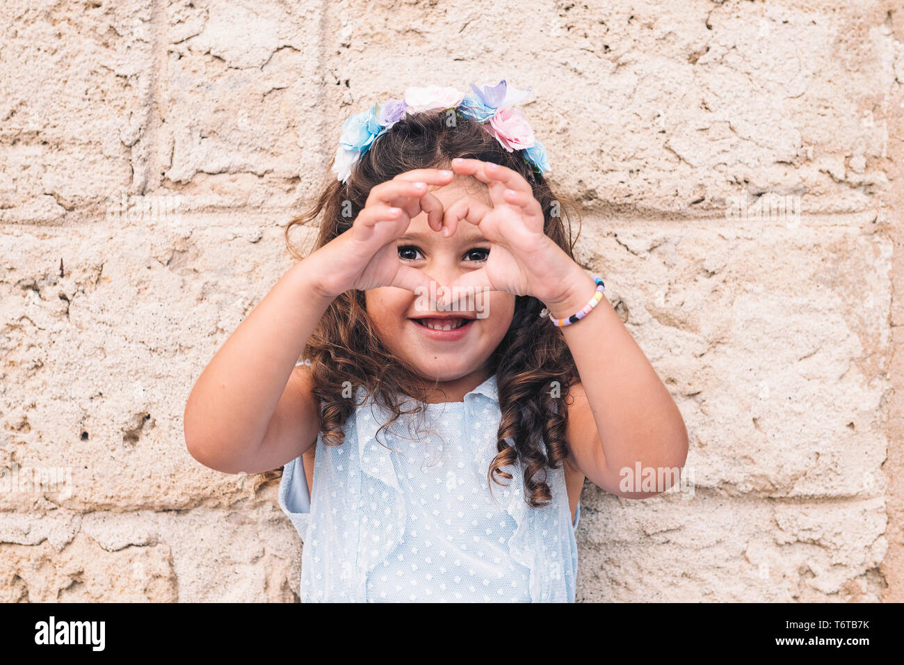 little girl making a heart with her hands, is in front of a stone wall and wears a blue dress and a flower headband - Stock Image