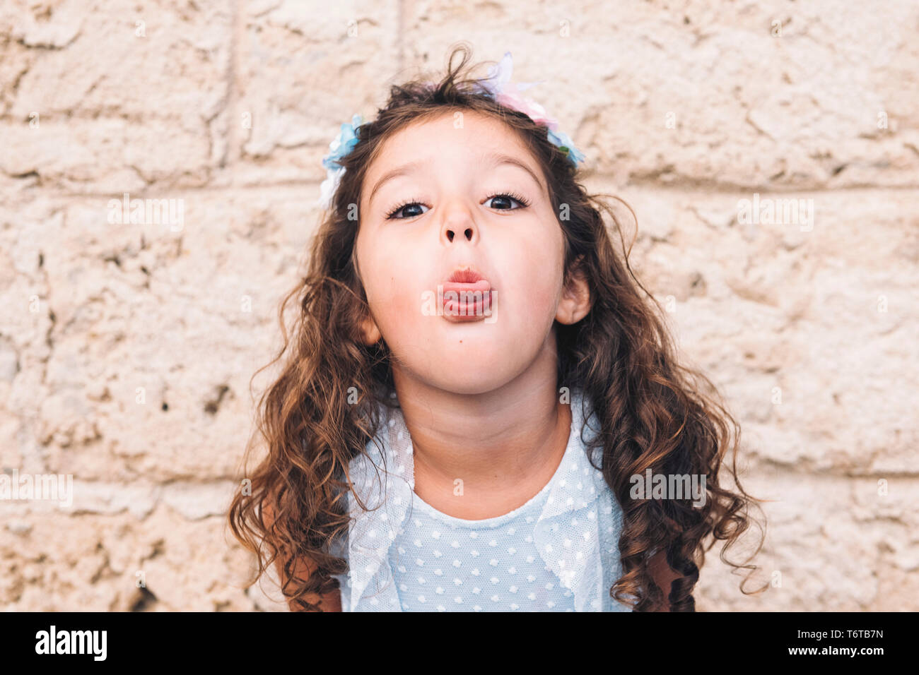 Teasing little girl sticking out her tongue, is in front of a stone wall and wears a blue dress and a flower headband Stock Photo