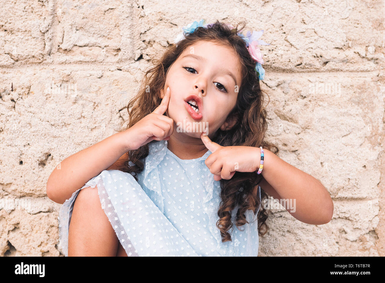 little girl making fun with hands and face, is in front of a stone wall and wears a blue dress and a flower headband - Stock Image