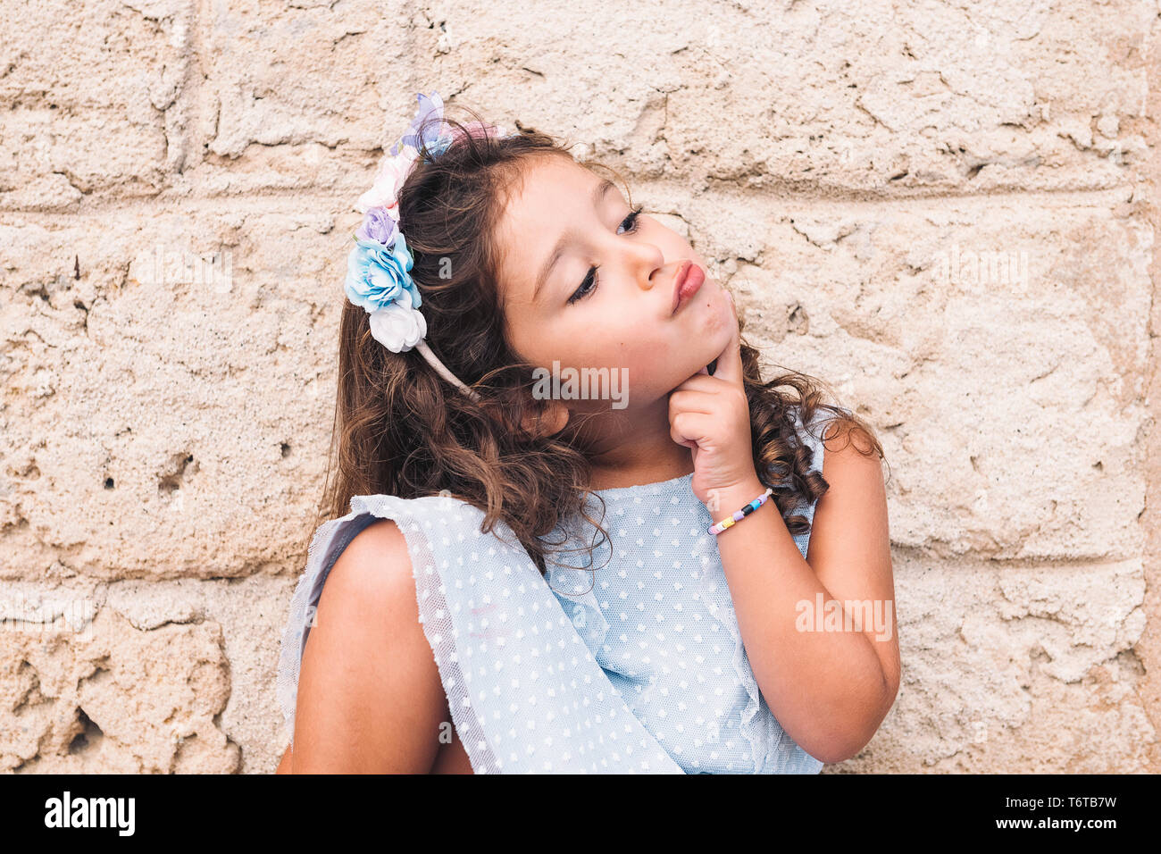 funny little girl doing like she thinks, is in front of a stone wall and wears a blue dress and a flower headband Stock Photo