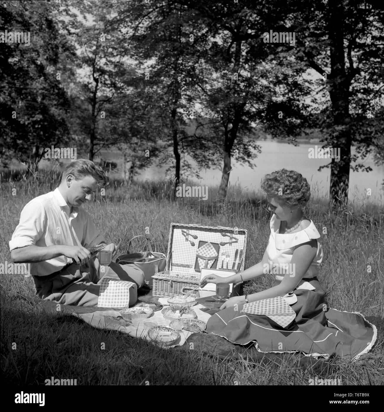 Picnic in the 1950s. A young couple are enjoying a sunny day. They have packed their food and drinks in the practical picnic case and are sitting on a blanket in the sun eating and drinking. Sweden 1956 Stock Photo