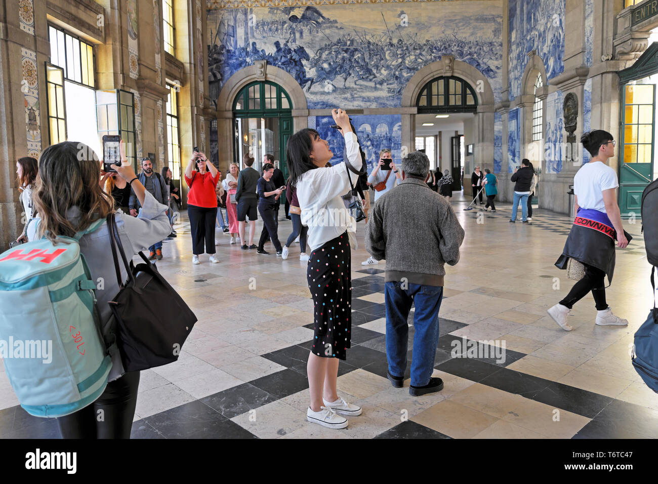 Tourist photographing azulejo tiles in the Central Hall of Sao Bento railway station train station in the city of Porto Portugal Europe KATHY DEWITT - Stock Image