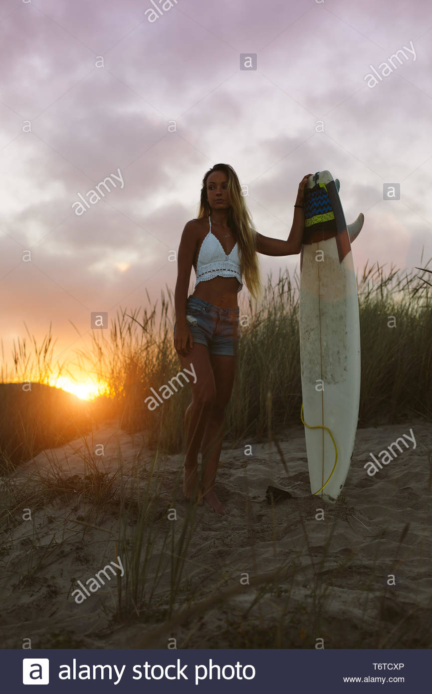 Young beautiful surfer standing at the beach with her surfboard in the morning against the sunrise. Natural girl on her way to the sea for surfing. Pl - Stock Image