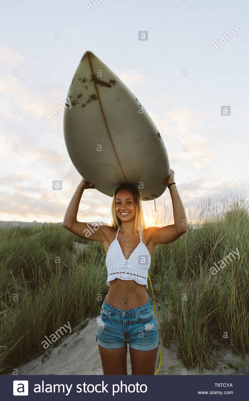 Young woman standing in the beach holding her surfboard over her head and smiling. Surfer backlit by the morning sunrise. Positive natural girl. - Stock Image