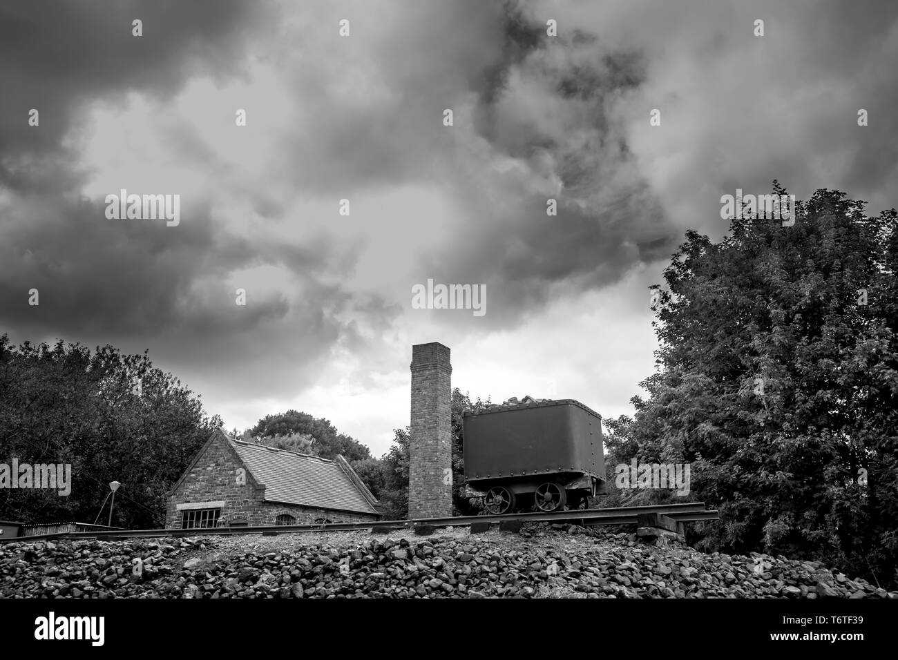 Moody, atmospheric, black and white, landscape photograph of dark clouds over coal mining colliery, Black Country Living Museum, Dudley, UK. No people. - Stock Image
