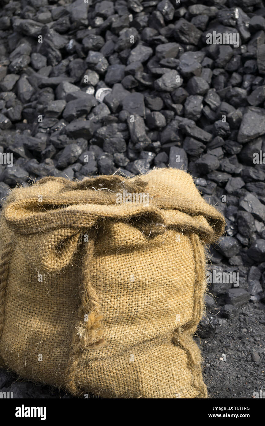 Portrait close up of a sack of coal on dirty, dusty ground outdoors with an enormous pile of loose coal behind. Black Country Museum colliery works. - Stock Image