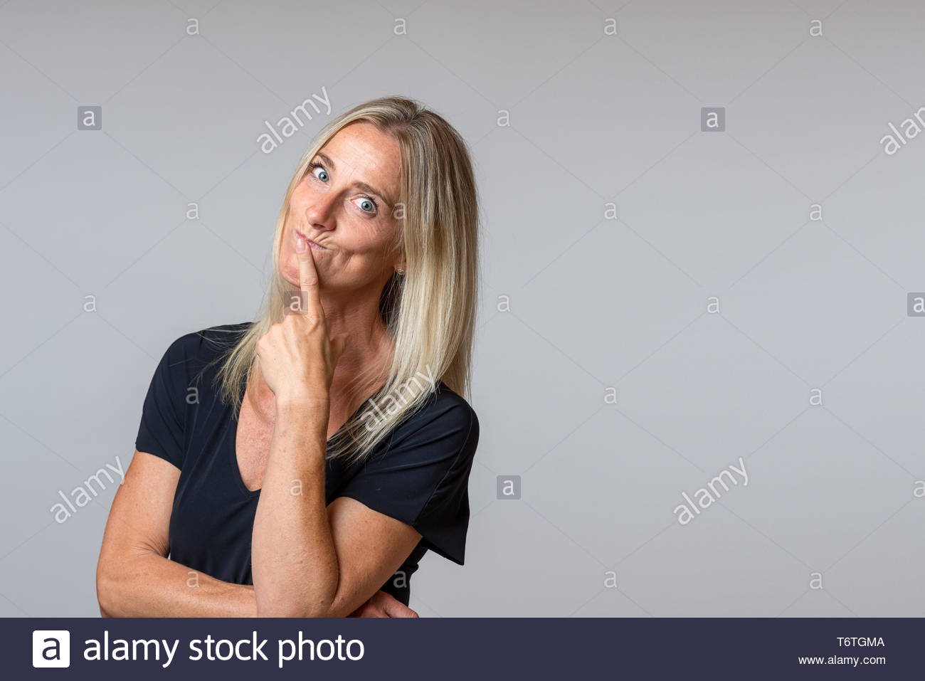 Speculative woman looking at the camera wide eyed - Stock Image