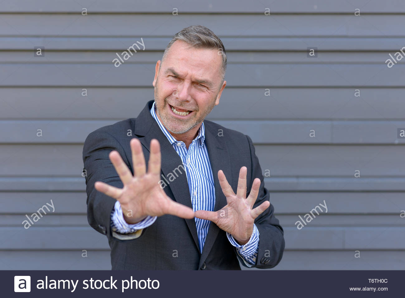 Businessman fending off something with his hands - Stock Image
