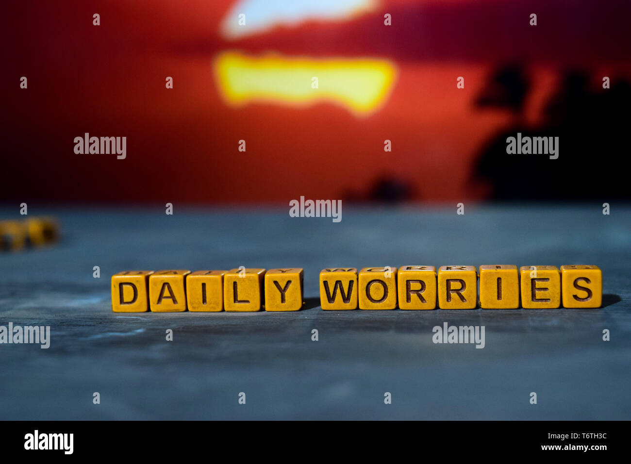 Daily worries on wooden blocks. Cross processed image with bokeh background - Stock Image