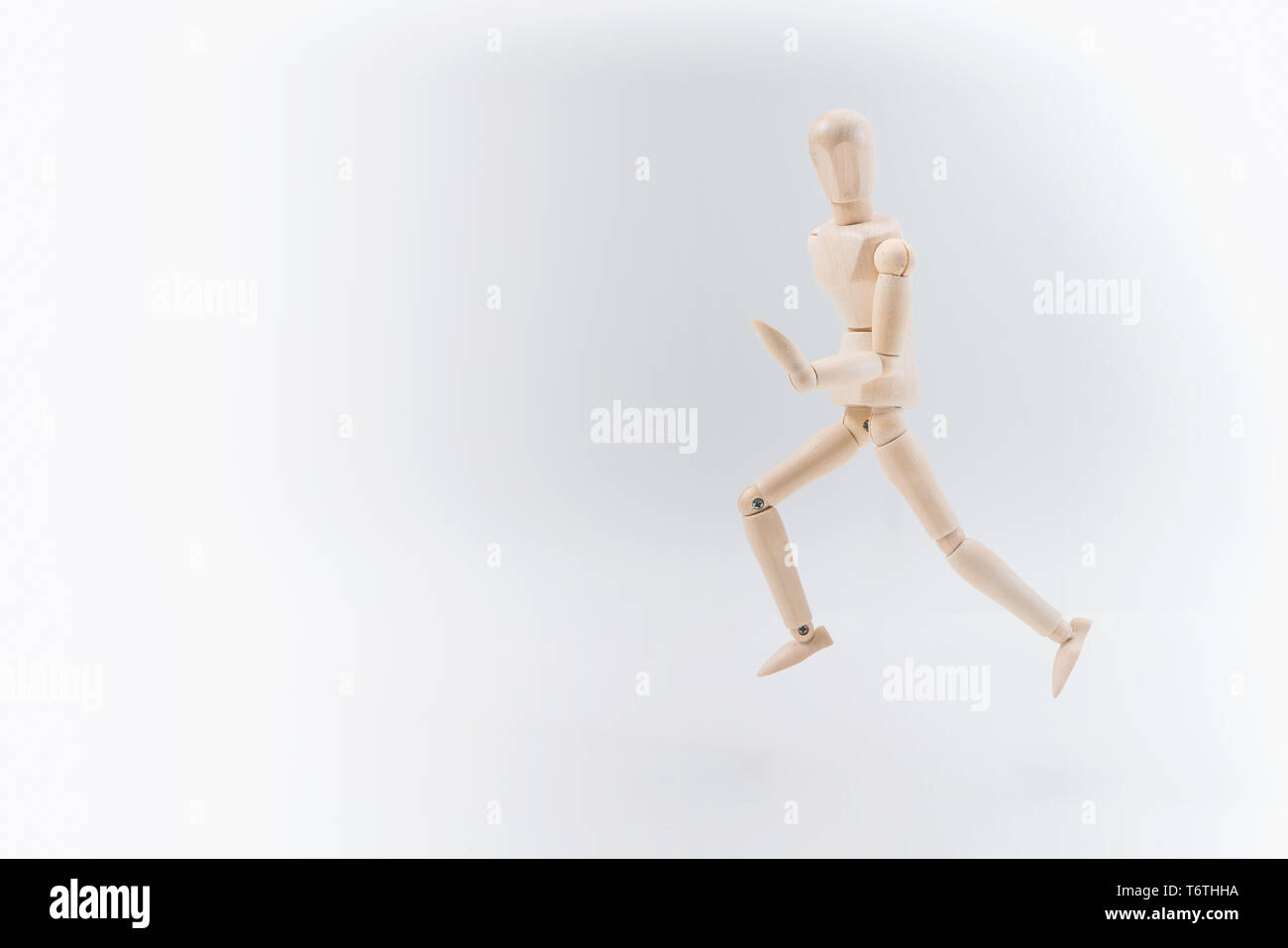Wooden dummy proudly presents some invisible thing, isolated on