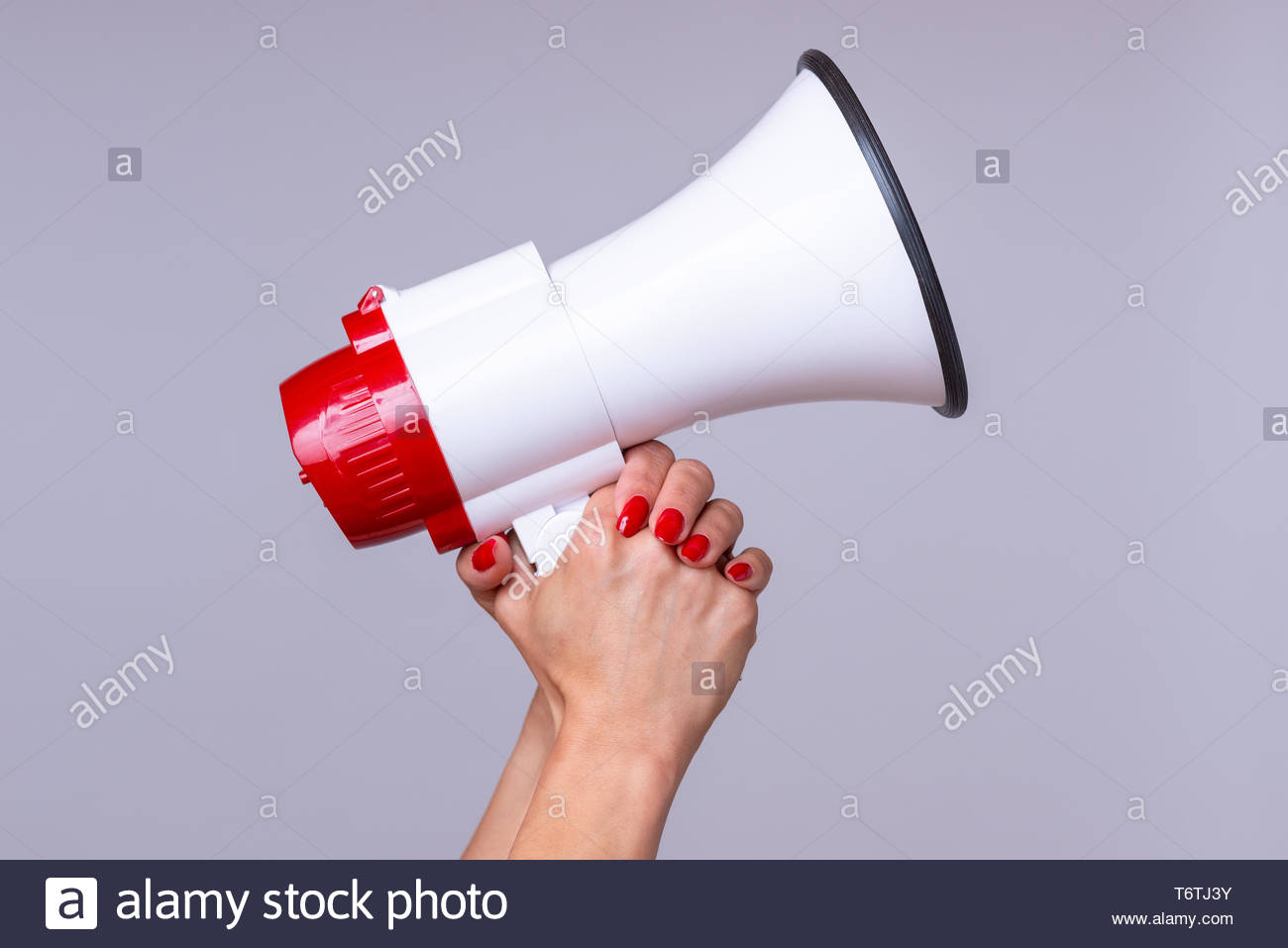 Woman holding up a loud hailer or megaphone - Stock Image