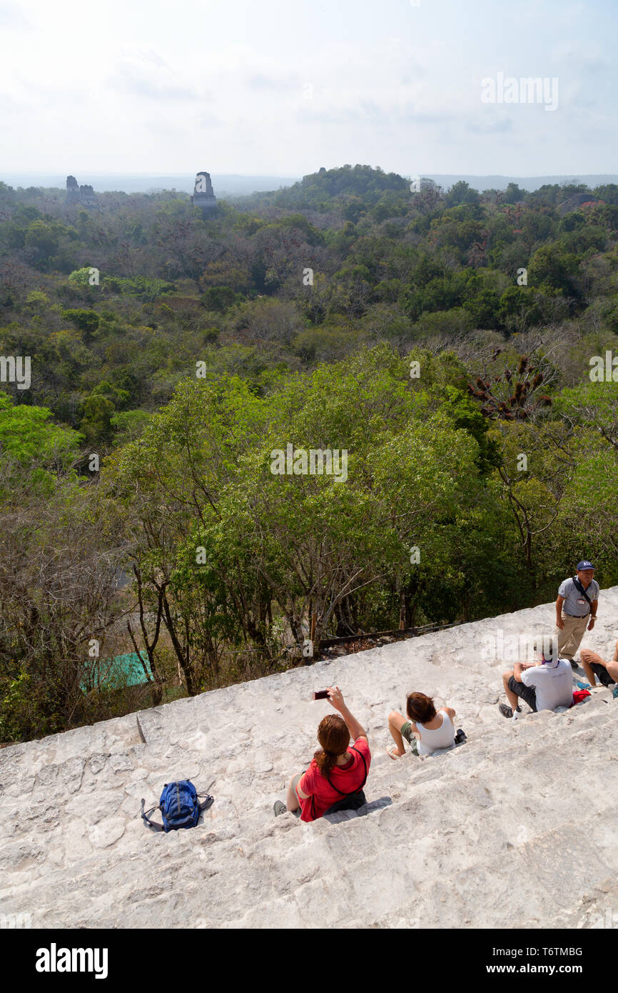 Tikal Guatemala - tourists at the top of Temple IV looking at other temples in the Mayan ruins; Tikal National Park, Tikal Guatemala Central America - Stock Image