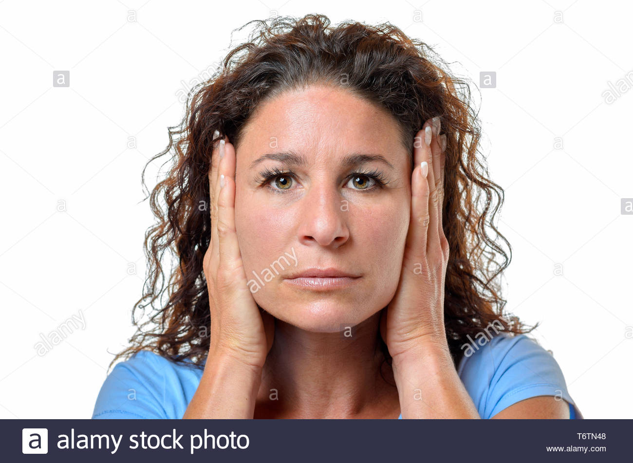Serious young woman blocking her ears Stock Photo