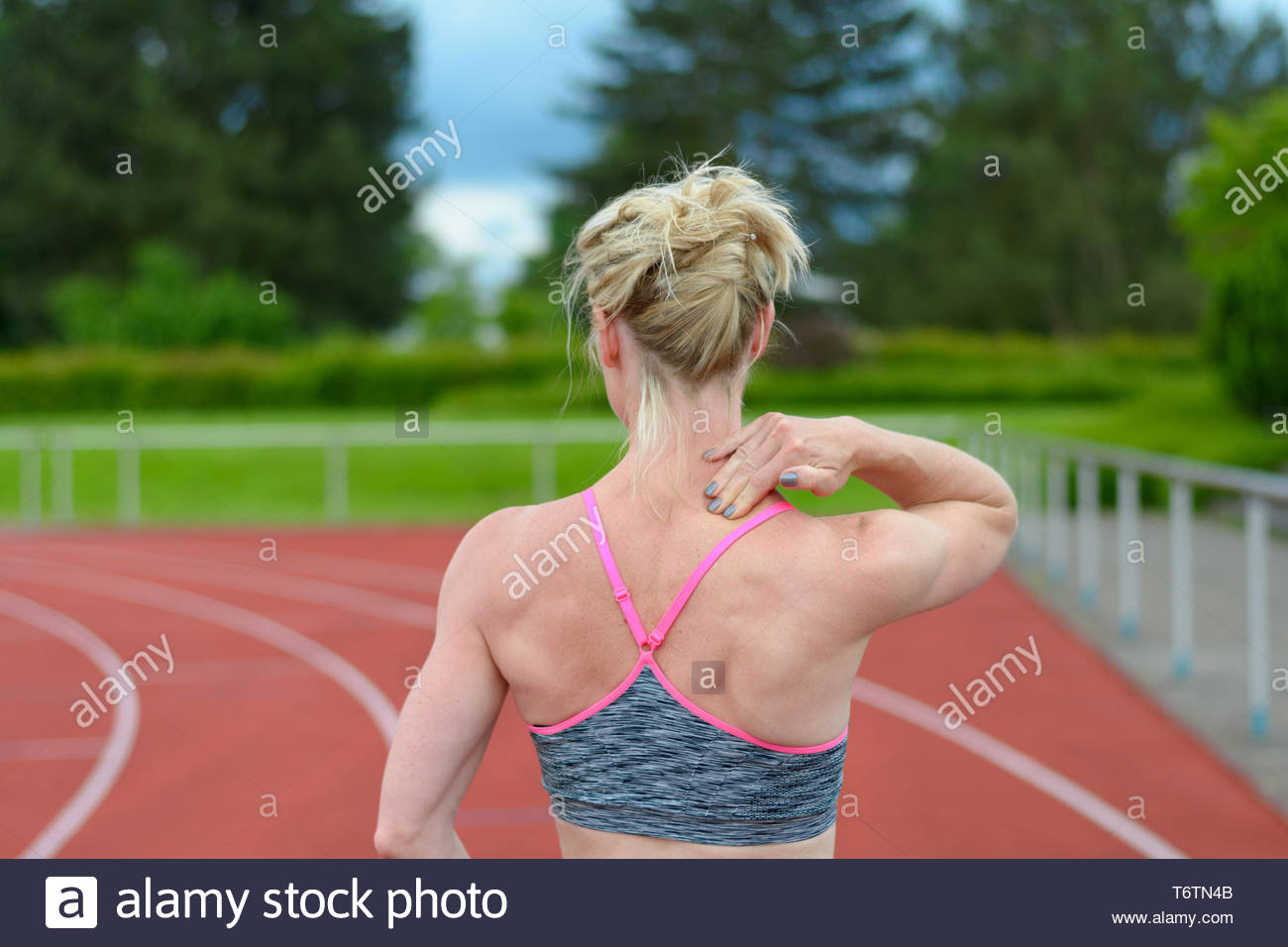 Rear view of sprinter massaging her own neck - Stock Image