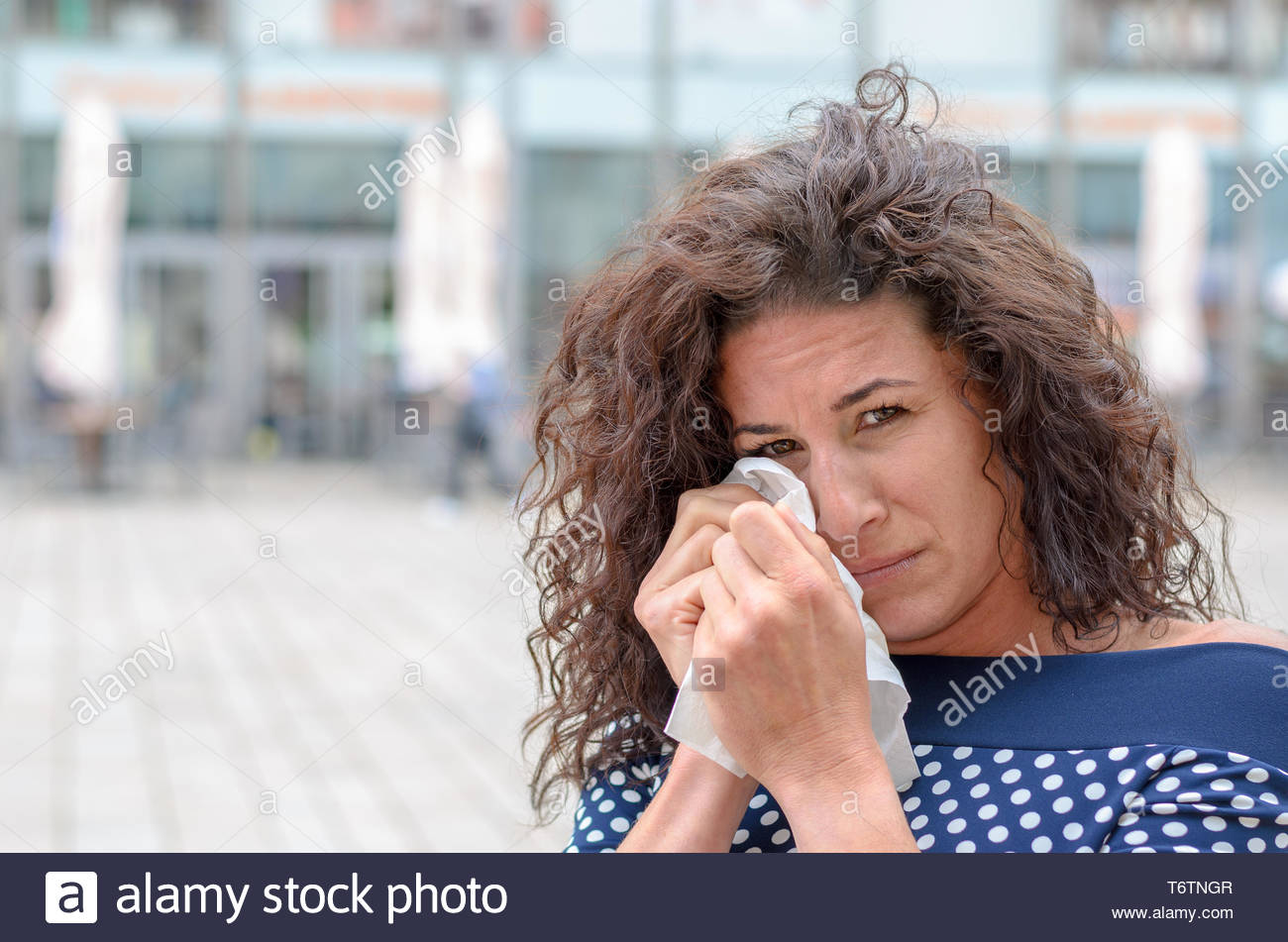 Tearful young woman wiping her eyes - Stock Image