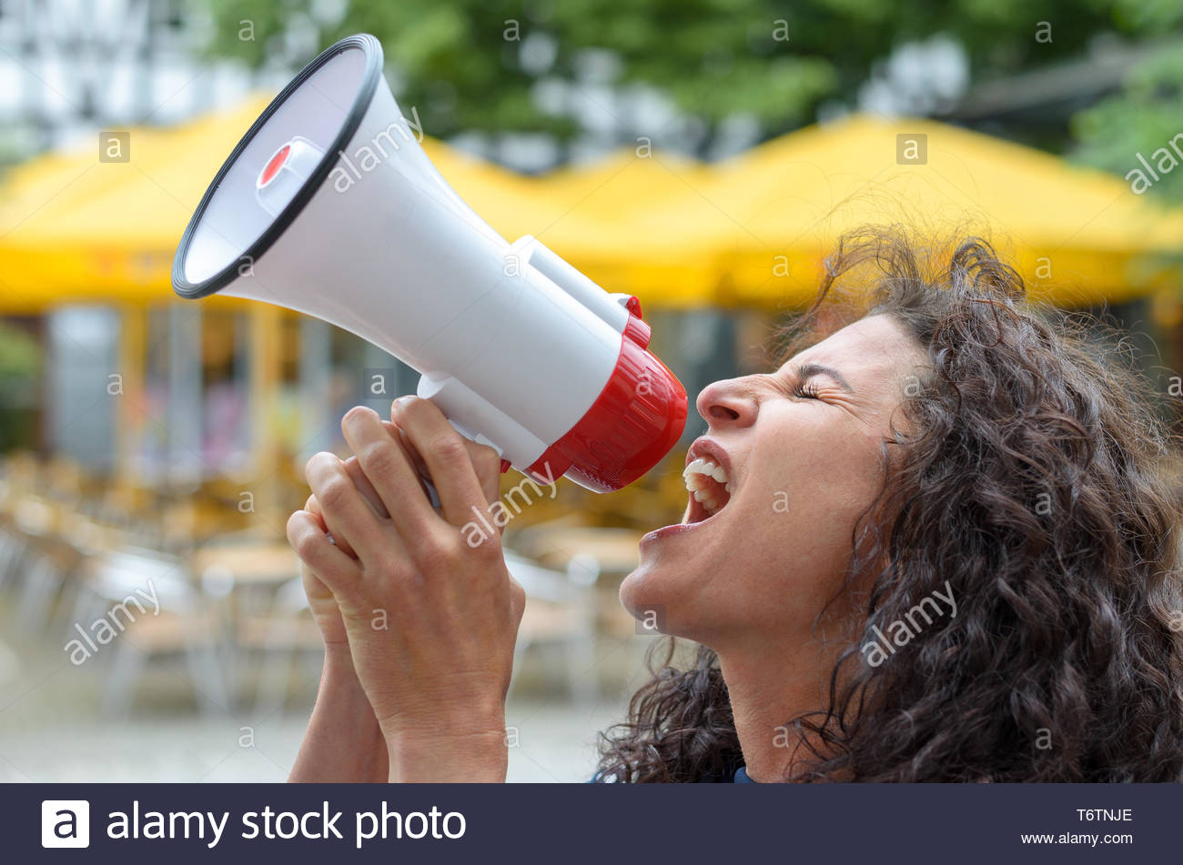 Angry young woman using a loud hailer - Stock Image