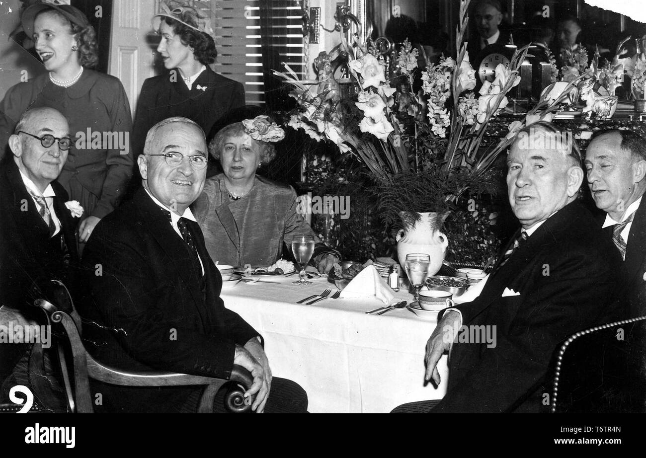 American President Harry Truman and Vice President Alben Barkley, both seated, turn toward the camera during an inauguration lunch, with Bess Truman, Margaret Truman and Marian Barkley Truitt at background left, Washington, DC, January 20, 1949. Image courtesy National Archives. () - Stock Image