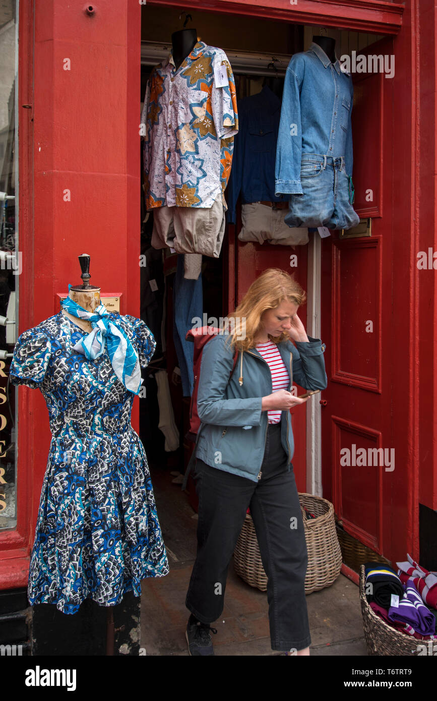 Customer leaving Armstrong's Vintage Clothing Emporium in the Grassmarket area of Edinburgh's Old Town. - Stock Image