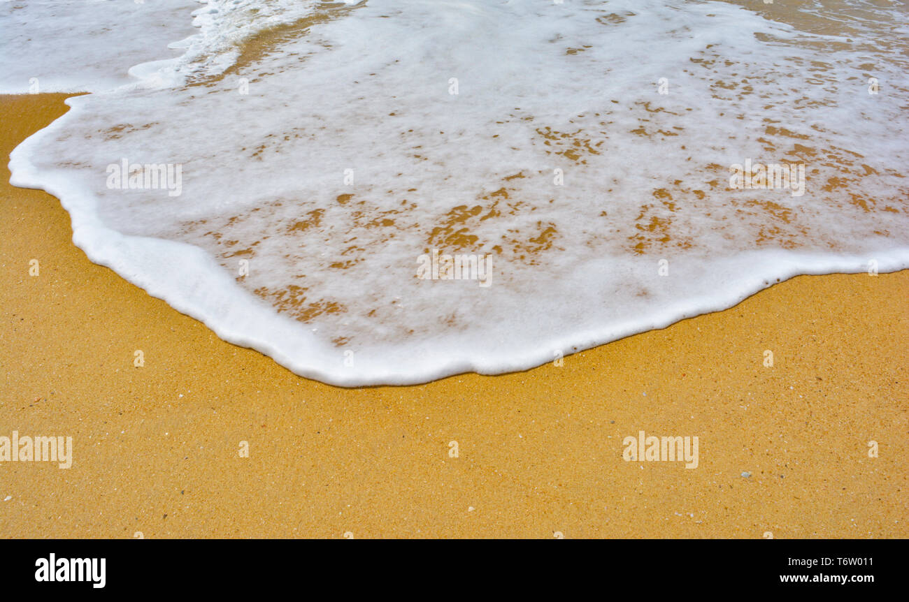 Soft wave lapped the sandy beach - Stock Image