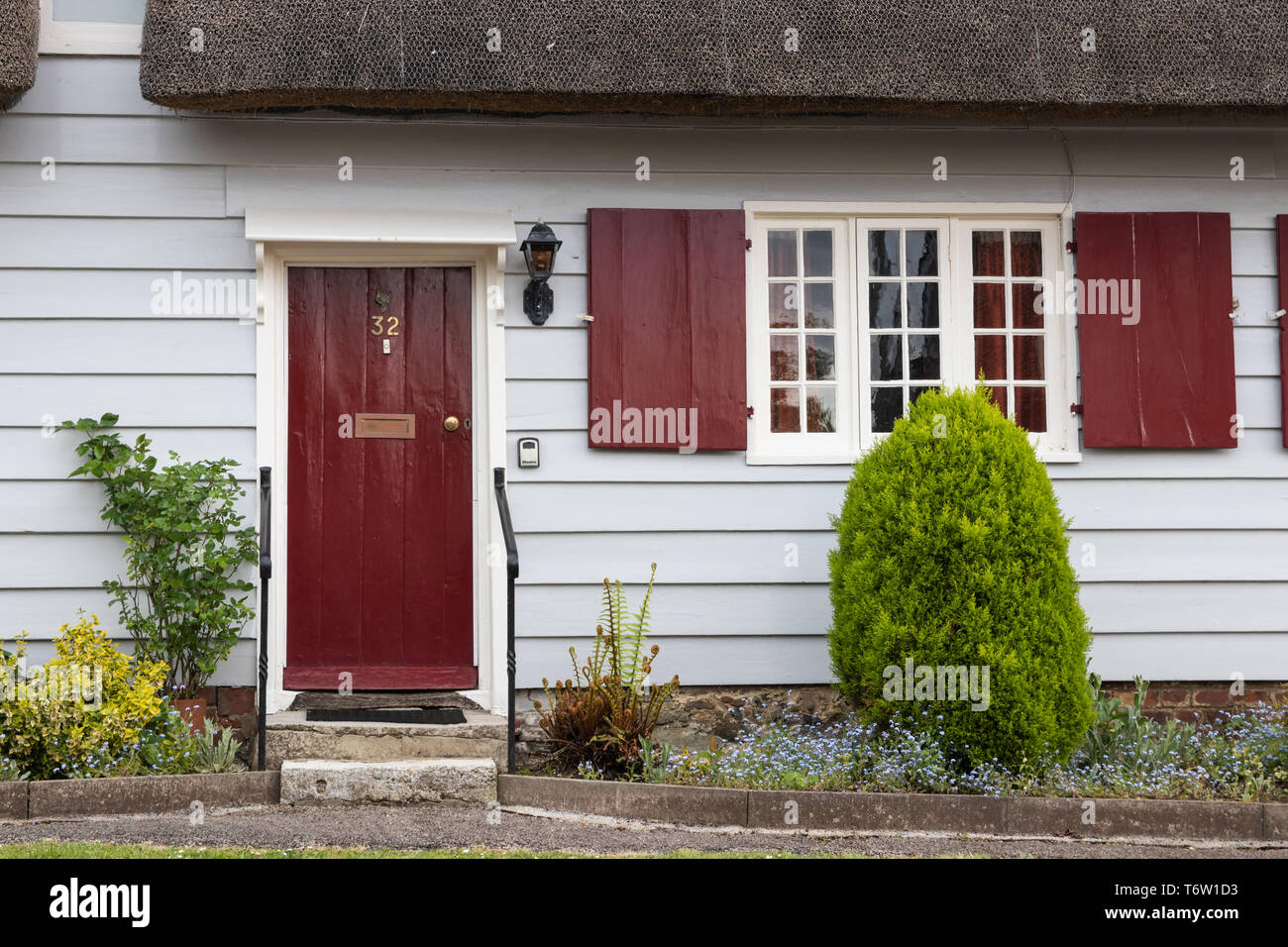 Traditional English thatched cottage entrance with red door - Stock Image