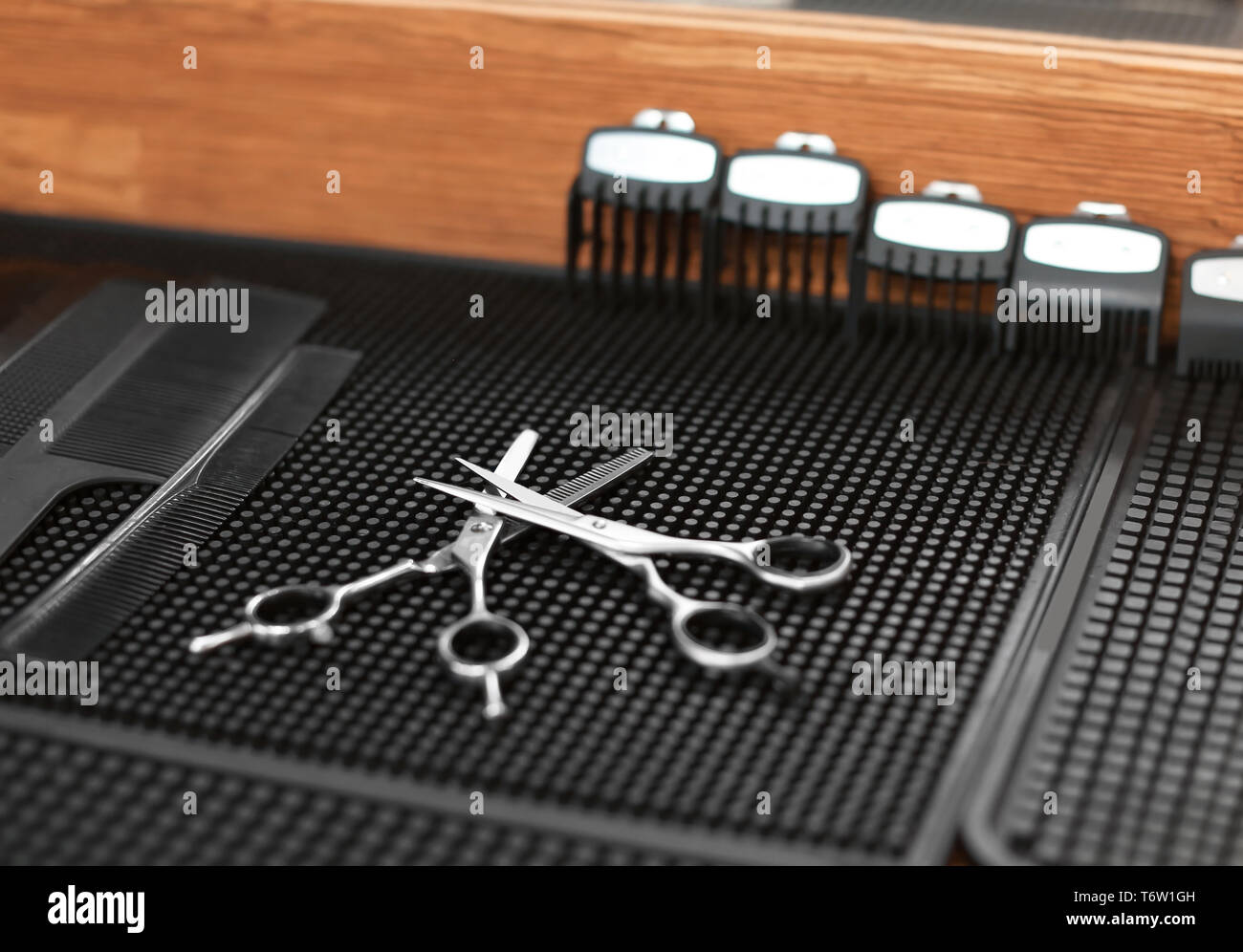 Trimmer attachment and scissors on table in hairdressing salon - Stock Image
