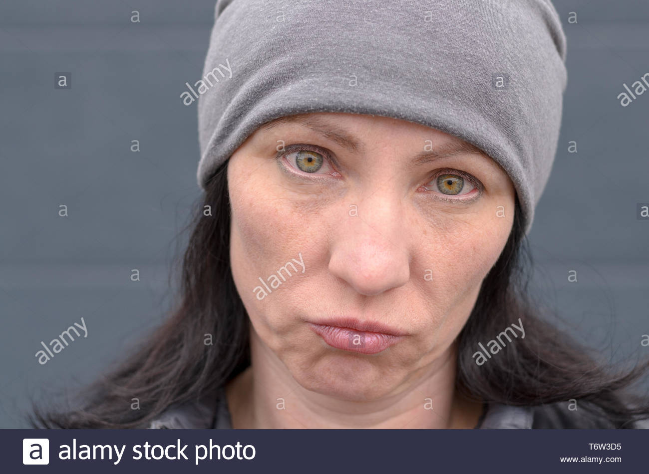 Dubious woman grimacing and looking at camera - Stock Image