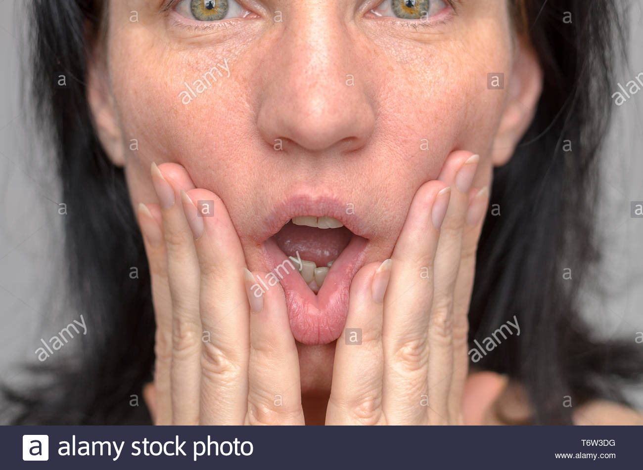 Woman squashing her face with her hands - Stock Image