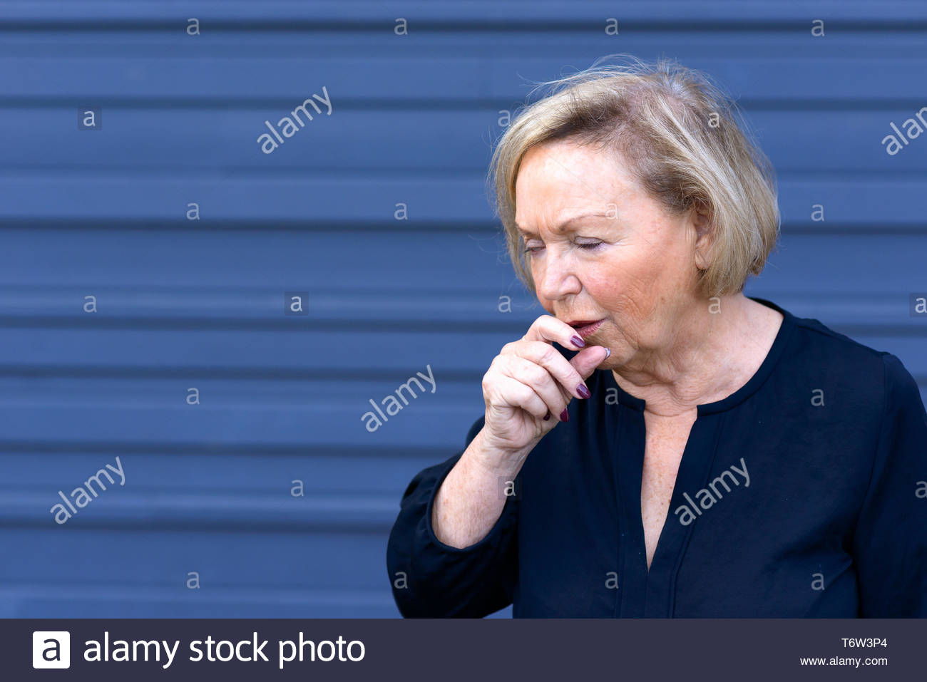 Unwell elderly lady having a coughing fit - Stock Image
