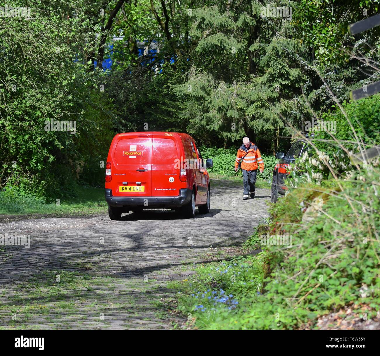 A postal worker on his way back to his van after delivering to a house in Thornsett, near New Mills, Derbyshire. - Stock Image