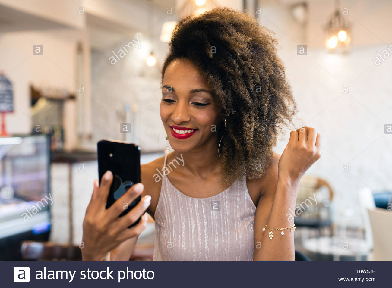 Stylish happy woman showing afro hairstyle taking a selfie photo with smartphone in a cafe bar . - Stock Image