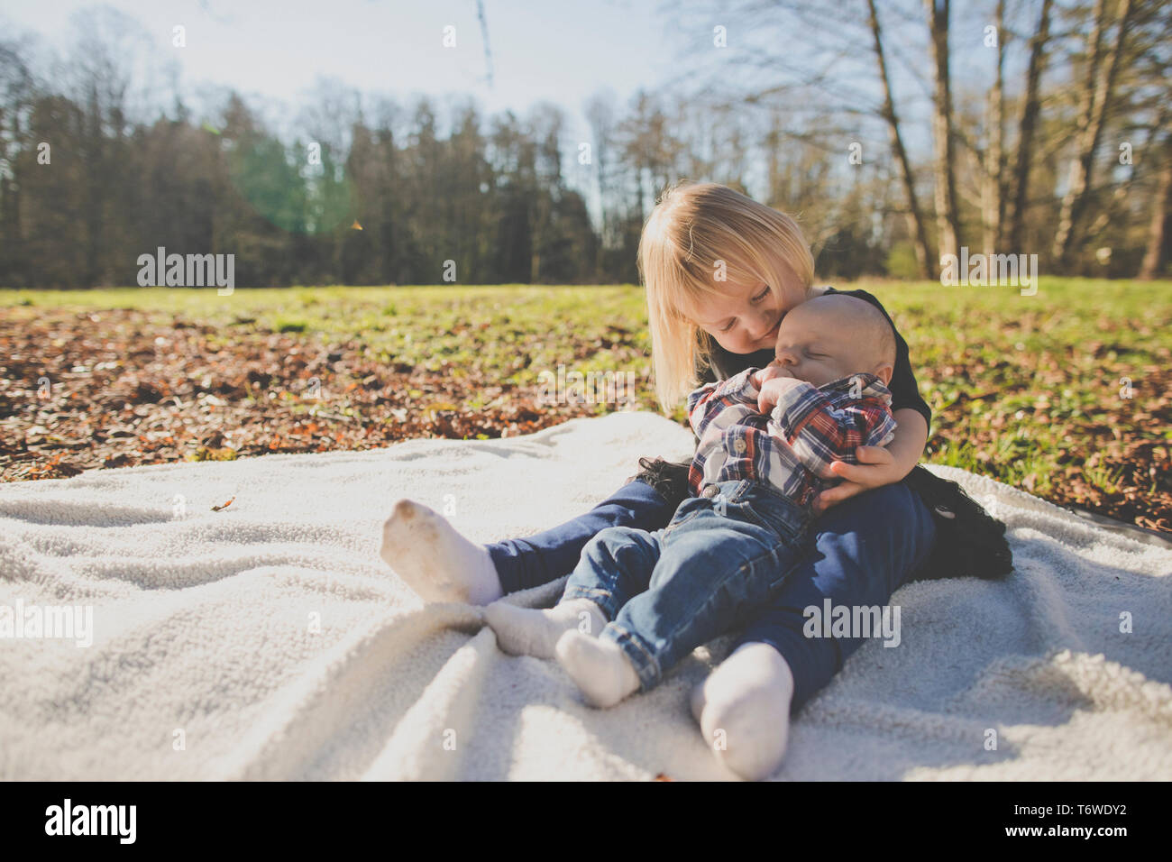 Sister holds her brother while on picnic blanket outside at park Stock Photo