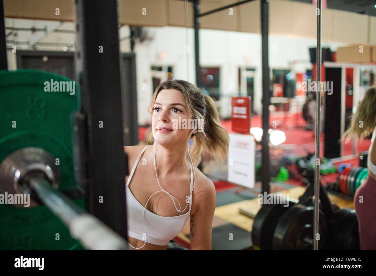 Woman preparing barbell in gym - Stock Image