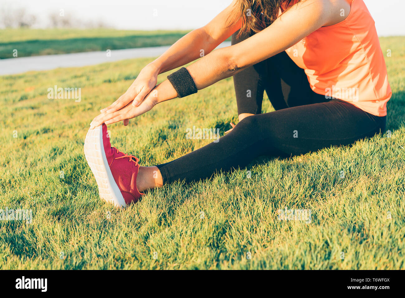 Young runner woman stretching legs before run in a park. Close up athletic and healthy girl wearing white and pink sneakers. Stock Photo
