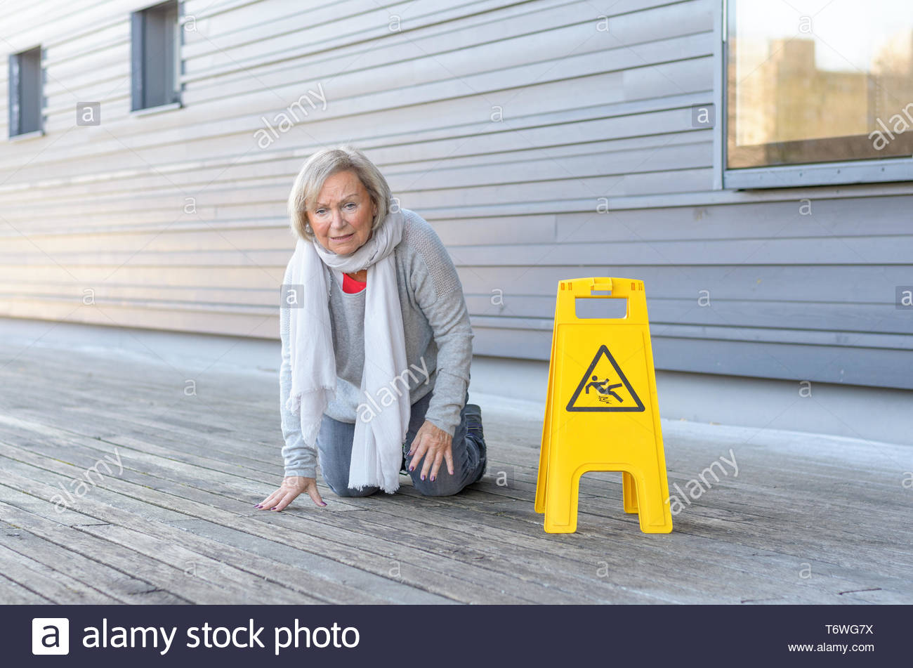 Elderly woman crawling on her knees after slipping - Stock Image
