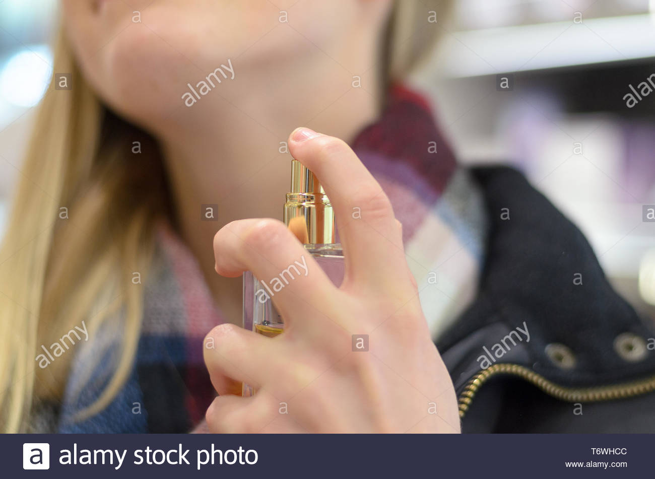 Young woman spraying her neck with perfume - Stock Image