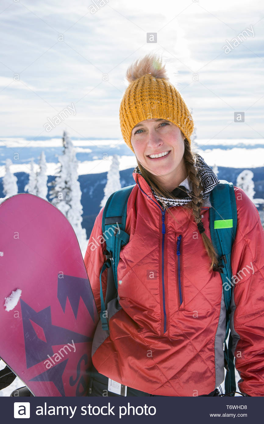 Winter portrait of adult woman holding snowboard in the mountains - Stock Image