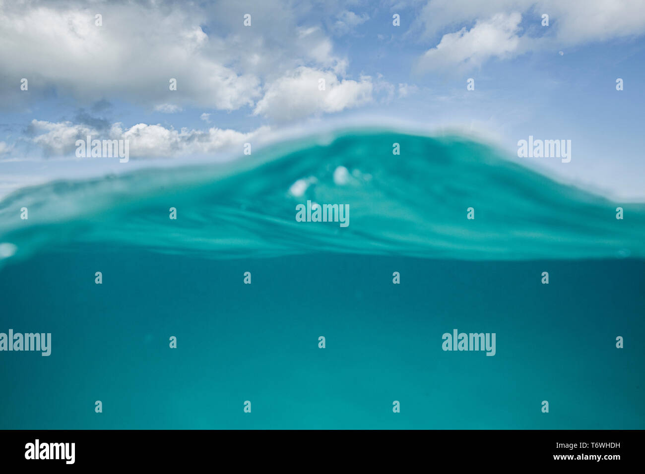 A split level shot of turquoise ocean water and clouds in a blue sky - Stock Image