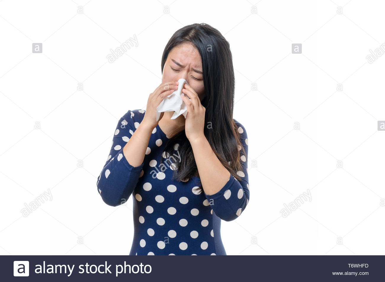 Unwell young Chinese woman blowing her nose - Stock Image