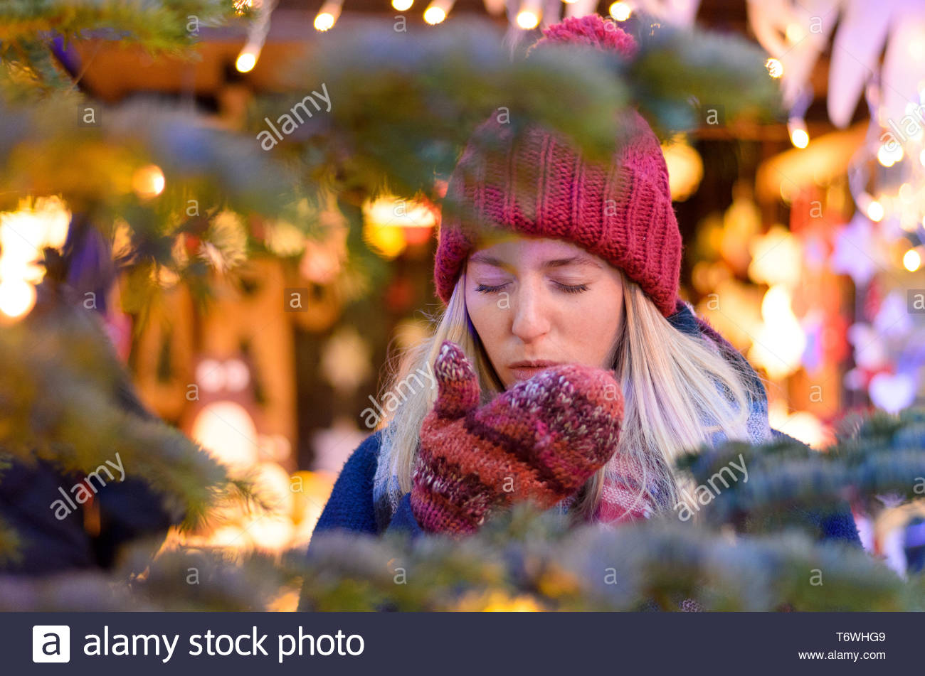 Cold young woman coughing on her gloved hands - Stock Image